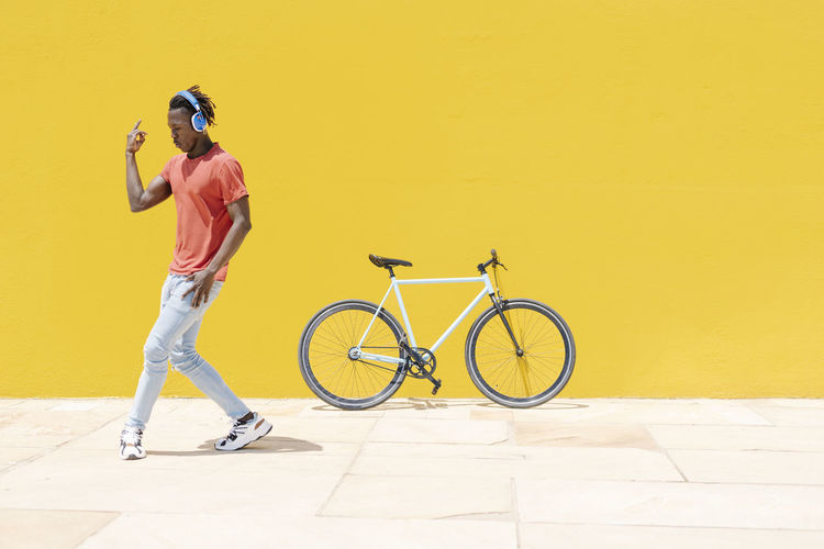Man with bicycle standing against yellow wall