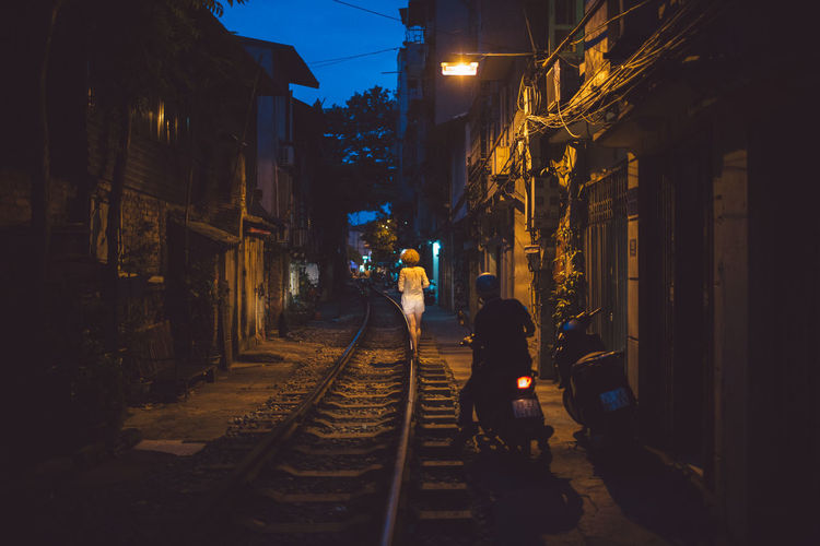 Woman walking on railroad track in city at night