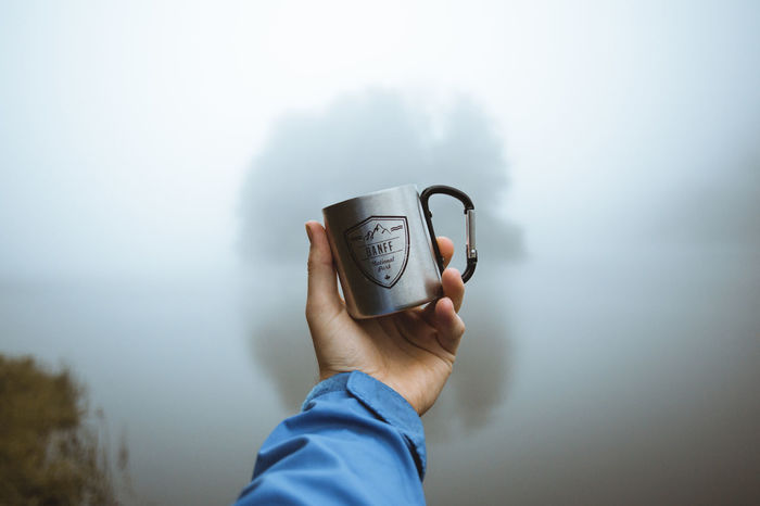 MAN HOLDING COFFEE CUP WITH WATER