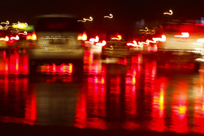 Reflection of the red brake light on a wet road when the street is crowded at night time Close-up Glowing Illuminated Night No People Outdoors Red Sky Water