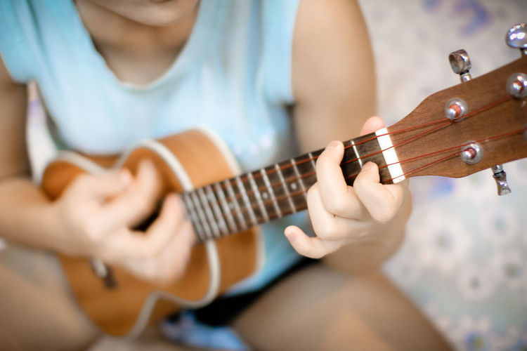Midsection of woman playing ukulele while sitting on bed