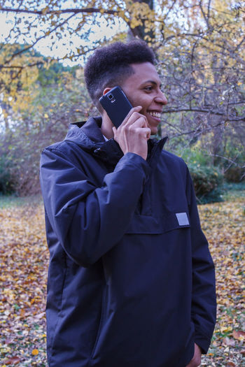 Man Talking On Phone While Standing In Forest
