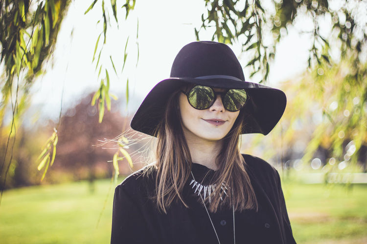 Portrait of young woman wearing sunglasses and hat while standing at park
