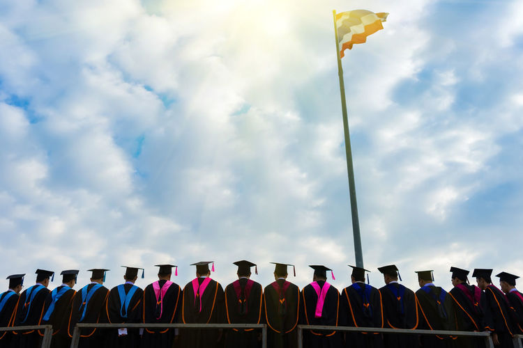 The graduates stand in-line to take group photo. Achievement Celebration Congratulations Graduation Happy Meeting Students Thailand Ceremony Cloud - Sky College Commencement Crowd Day Finish Flag Graduates Group Photo Low Angle View Nature Outdoors School Sky Uniform University
