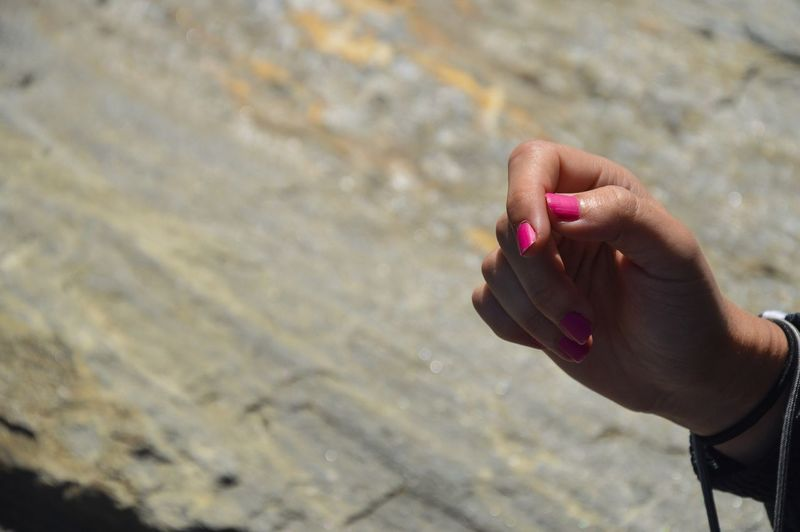 Close-up of woman hand holding water at beach