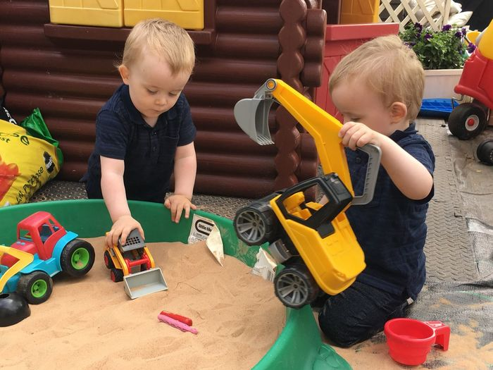 Brothers playing with toys at yard