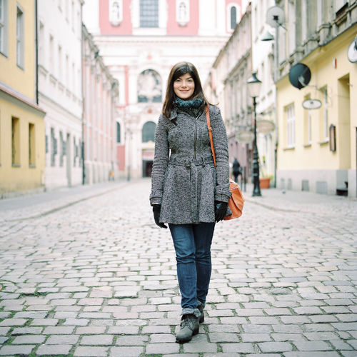 Portrait of woman in warm clothing standing on cobbled street in city