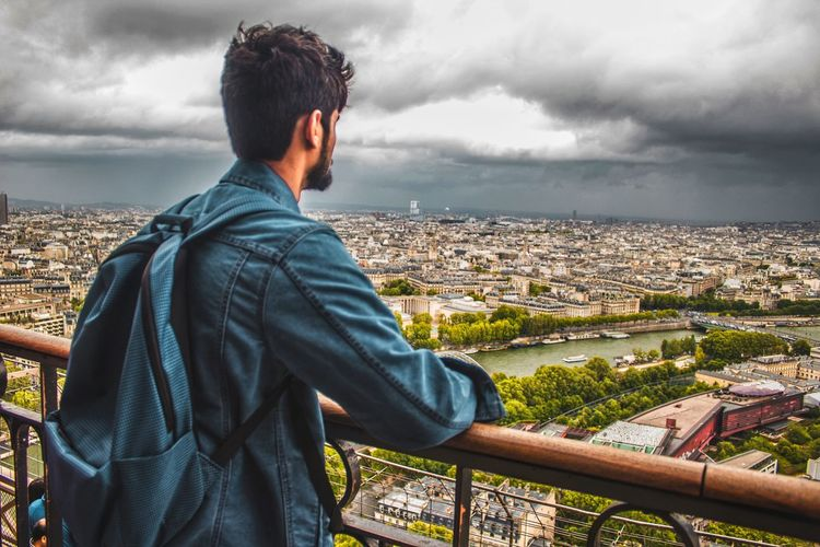 Man standing at observation point against cityscape