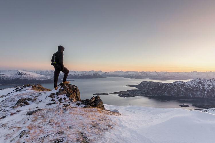 Man standing on snowcapped mountain against sky during winter