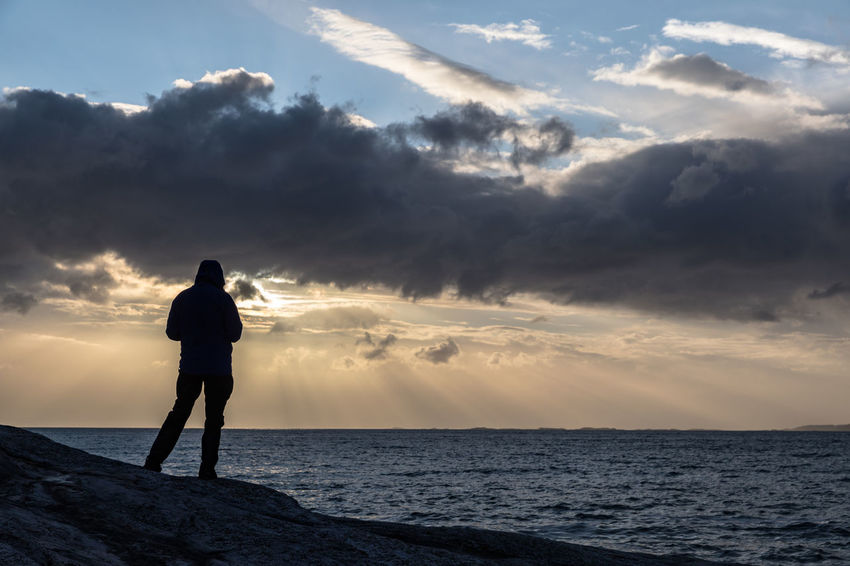 Man standing on rocks looking towards sunset over sea Cloudscape Dramatic Sky Norwegian Sea Rock Formation Sunlight Atmospheric Mood Beauty In Nature Cloud - Sky Full Length Horizon Over Water Men Nature Nordland County One Man Only One Person Outdoors Rear View Relaxation Remote Sea Silhouette Sky Standing Sunbeam Sunset