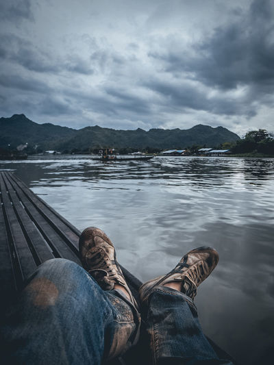 Low section of man relaxing on pier over lake against cloudy sky