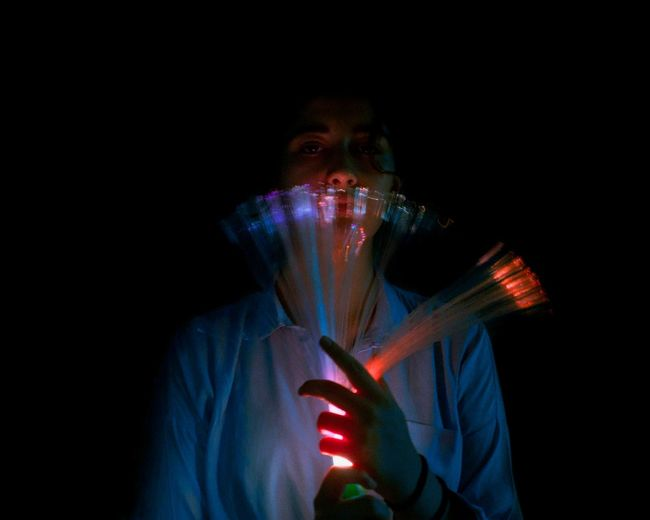 Portrait Of Woman Holding Illuminated Lighting Equipment Against Black Background