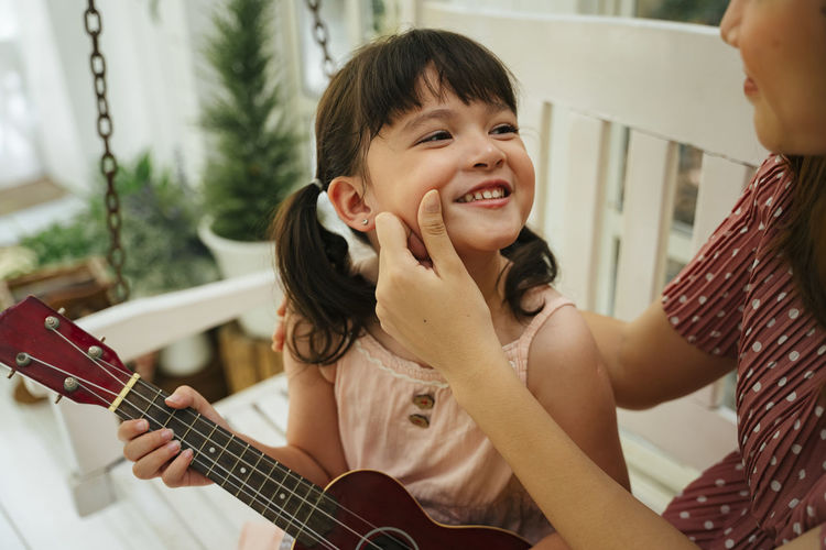 Portrait of smiling boy playing guitar