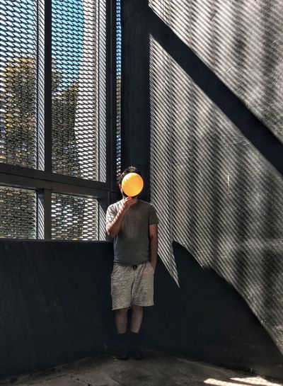 Front view of man holding yellow balloon against windows and wall.