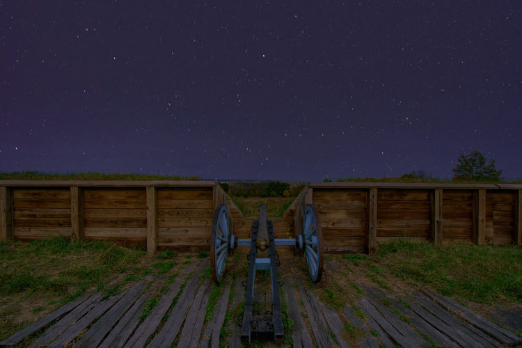 Digital composite image of field against sky at night