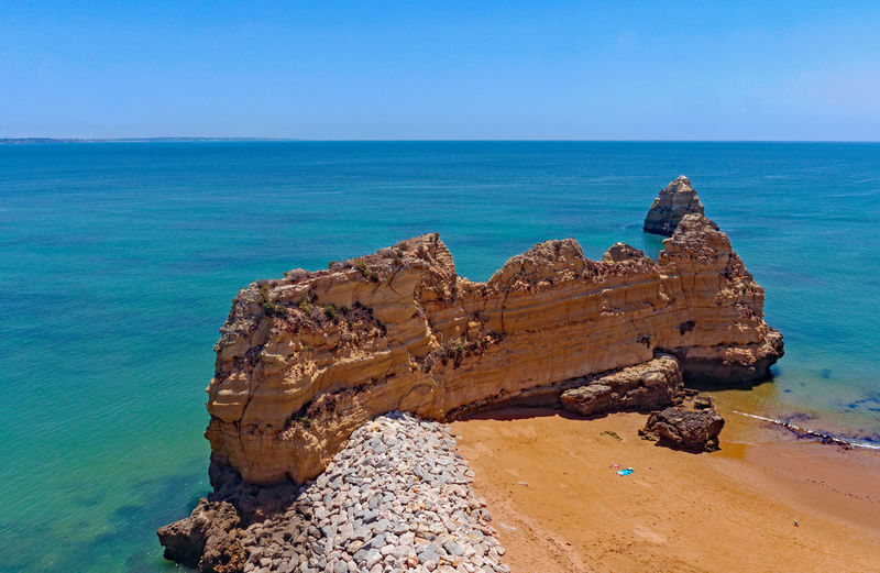 Rock formation on beach against blue sky