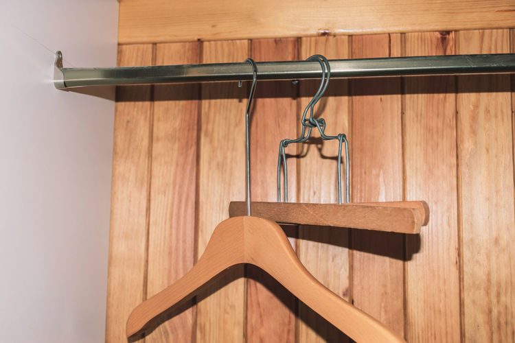 Close-up of coathanger hanging by wall at home