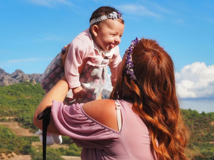 Close-up of mother holding happy daughter against blue sky