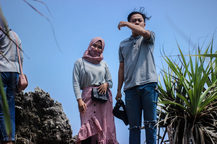 Low angle view of man and woman standing by plants against sky
