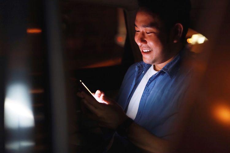 Smiling man using mobile phone at night