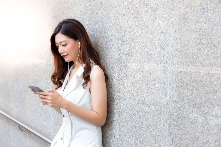 Beautiful young woman using mobile phone against wall