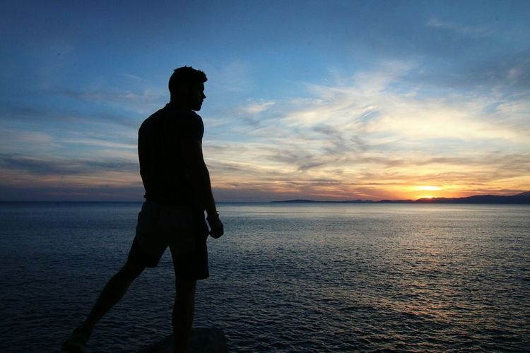 Silhouette Man Looking At Sea During Sunset