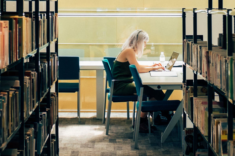Adult Adults Only Book Bookshelf Chair Day Desk Education Full Length Indoors  Learning Library Literature One Person People Shelf Sitting Student University Women Working Young Adult Young Women