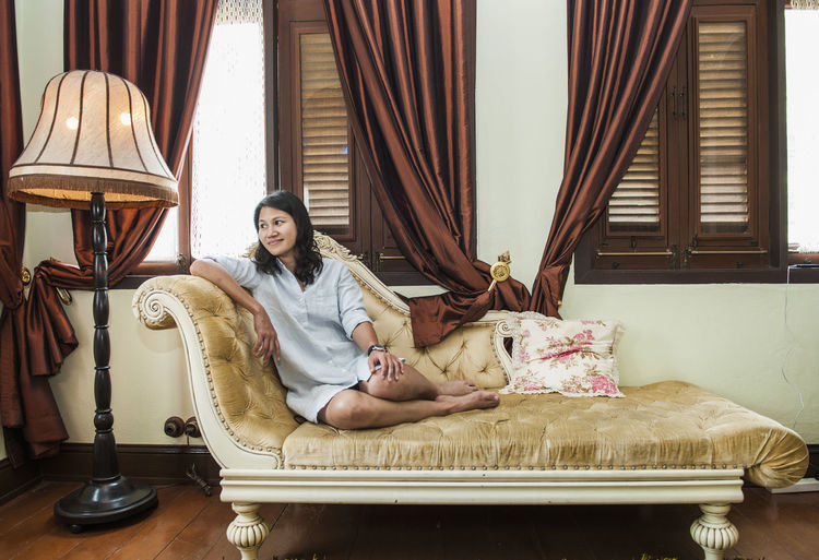 Full Length Of Smiling Beautiful Woman Resting On Chaise Longue At Home