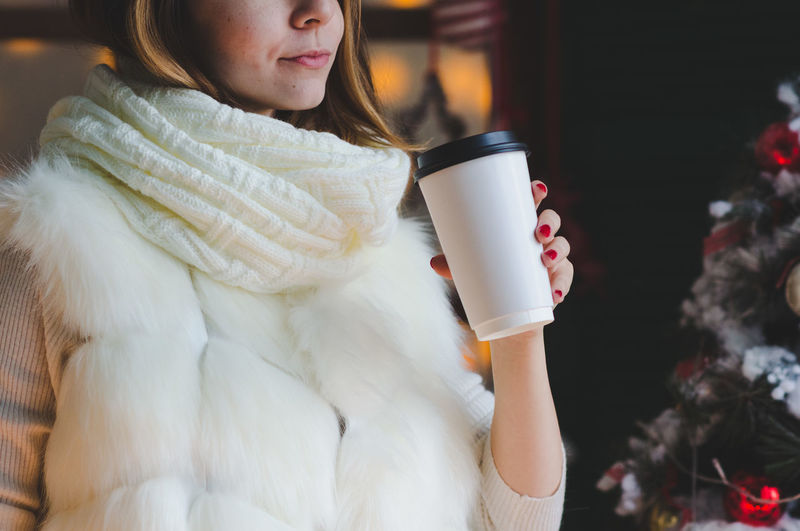 Midsection Of Woman Having Coffee During Christmas