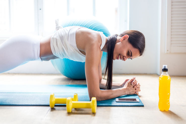 Smiling young woman exercising at home