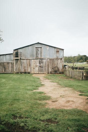 Abandoned barn on field against clear sky
