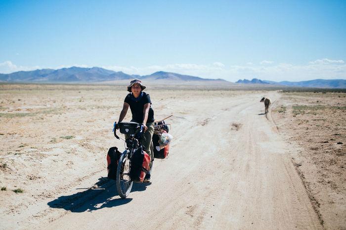 MEN RIDING MOTORCYCLE ON DESERT