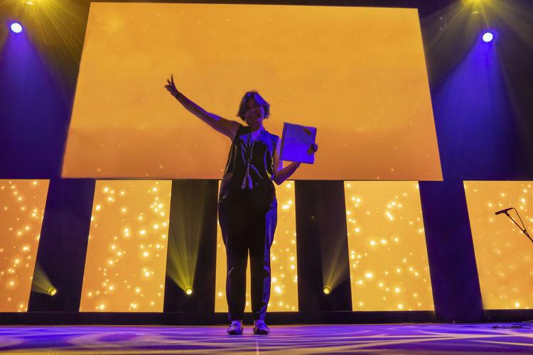 Full length of woman standing against illuminated lighting equipment