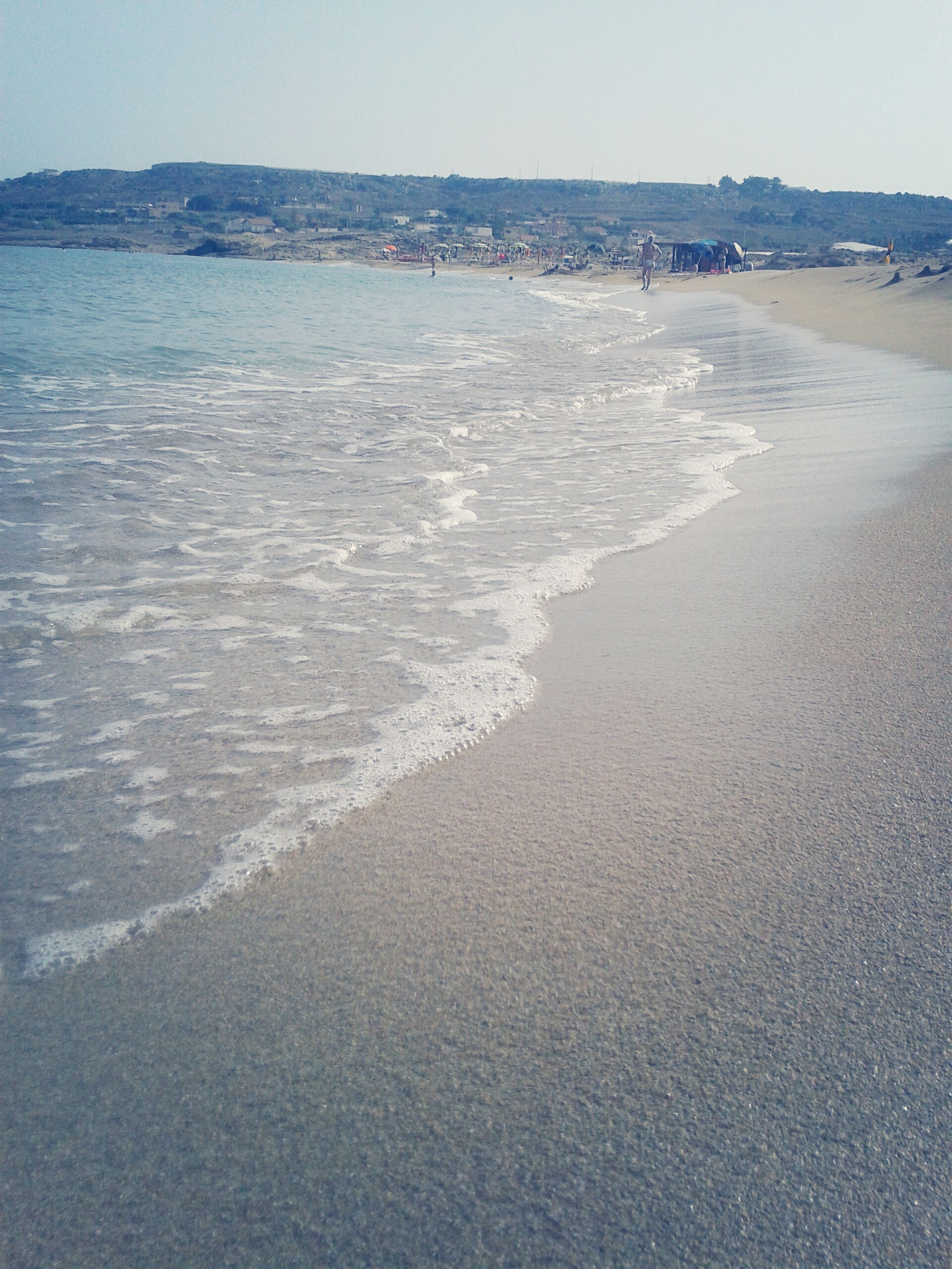 sea, beach, water, sand, shore, horizon over water, wave, scenics, tranquility, surf, tranquil scene, beauty in nature, nature, coastline, incidental people, sky, clear sky, day, idyllic, vacations