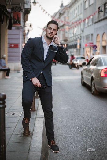 Portrait of businessman talking on mobile phone while standing in city