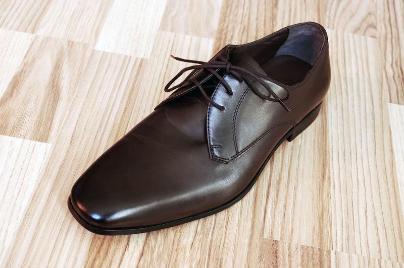 Close-up of leather shoe on hardwood floor