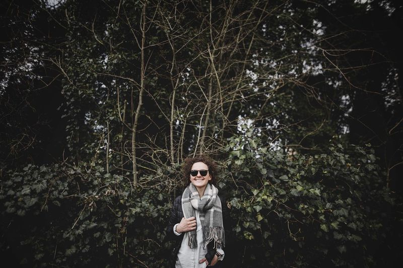 Portrait of young woman wearing scarf standing against trees in forest