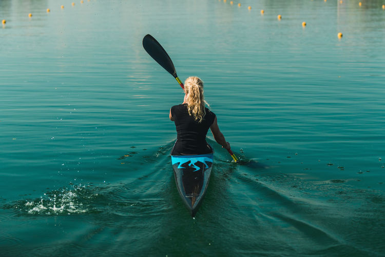 Rear view of woman kayaking in lake