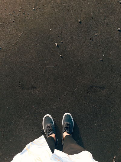 Low Section Of Woman Standing On Black Sand At Beach