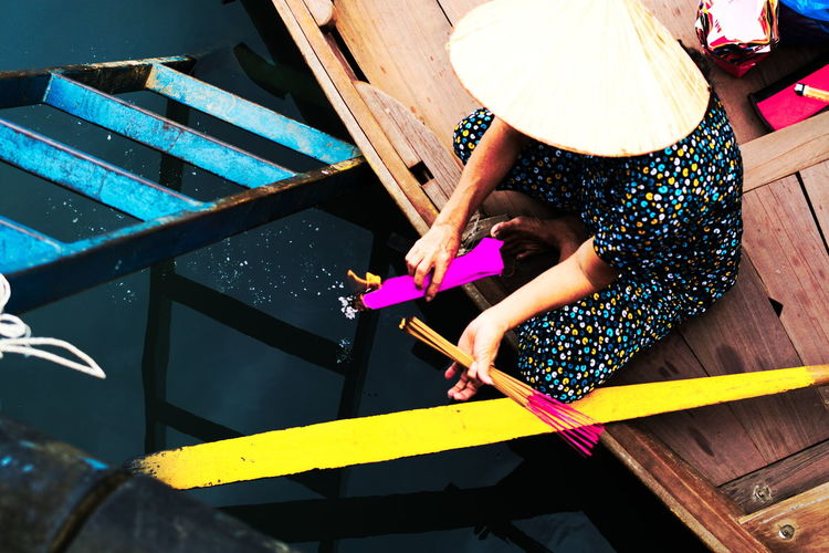 High Angle View Of Woman Burning Incense Sticks In Boat