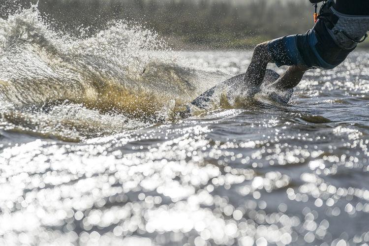 Low section of man splashing water in sea