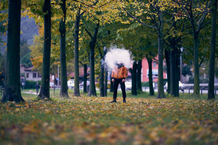 Man smoking while standing by trees during autumn