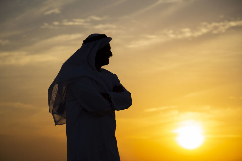 Side view of man in traditional clothing standing against sky during sunset