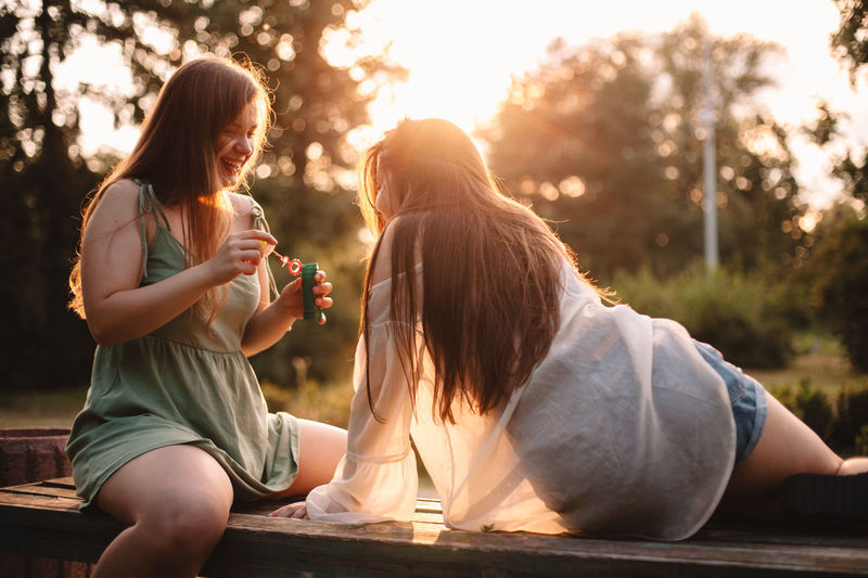 Young woman drinking water while sitting outdoors