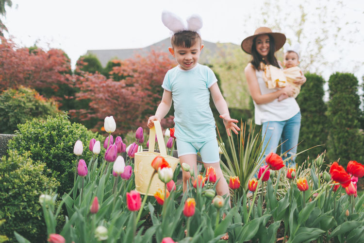 Smiling woman looking at son playing in garden