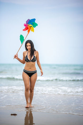 Beach Sea Water Land Standing One Person Beauty In Nature Young Adult Horizon Over Water Sky Lifestyles Young Women Real People Full Length Front View Horizon Holding Nature Beautiful Woman