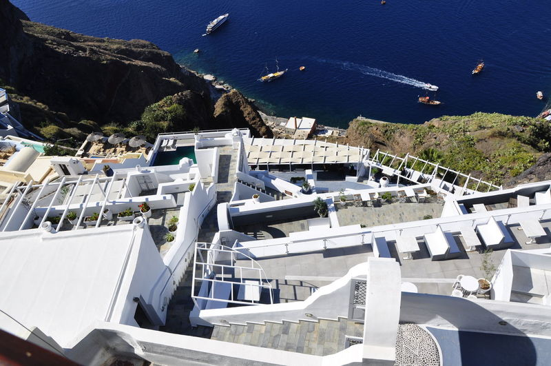 Architecture Beauty In Nature Building Exterior Built Structure Cliff Cliffs Day Green Color Hills Looking Down Nature No People Outdoors Roof Santorini Sunlight Traveling Adapted To The City Medditeranean