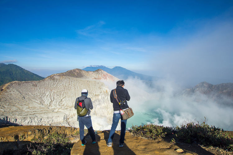 INDONESIA Travel Adventure Beauty In Nature Blue Sky Casual Clothing Day Environment Full Length Kawah Ijen Landscape Leisure Activity Lifestyles Men Mountain Mountain Range Nature Non-urban Scene Outdoors People Real People Scenics - Nature Sky Standing Tourism Two People