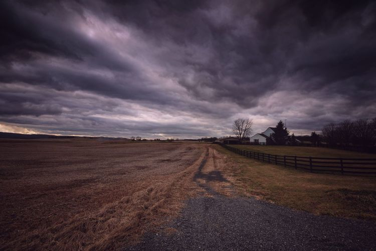 Scenic view of field against dramatic sky