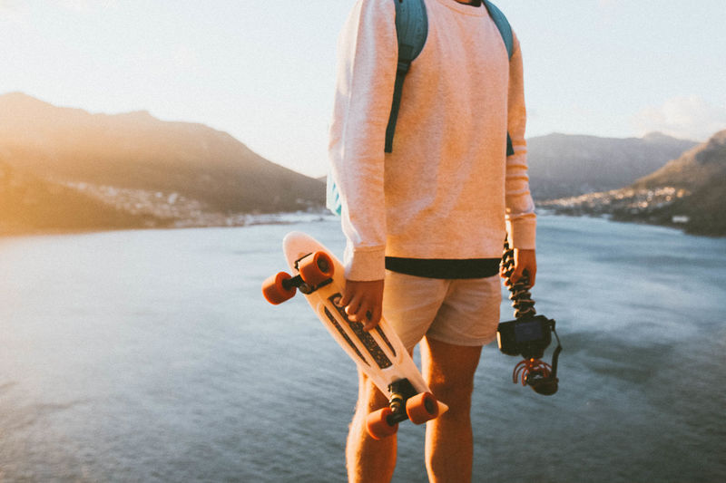 Midsection of man holding skateboard and camera against lake